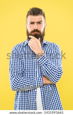 Needing a barber to shape the beard. Bearded man thinking of visiting barber. Thoughtful hipster touching unshaven chin before going to barber shop. Trimming a beard like a master barber.