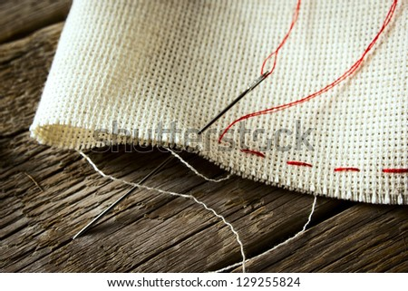 needle and natural linen canvas texture for the background on wooden table