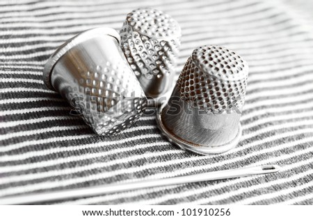 Needle and thimbles on a fabric.