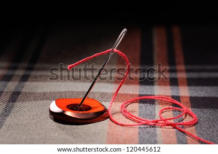 Needle and thread on a checkered fabric