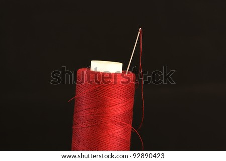 needle with a red thread on a black background