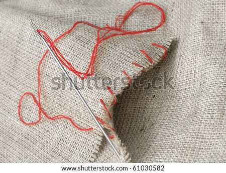 Needle with red thread that executes the stitches on sacking