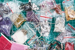 needlecraft background - top view of various items, beads, bugles, spangles, threads, gimps for embroidery close up