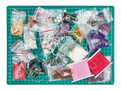 needlecraft background - top view of various items, beads, bugles, spangles, threads, gimps for embroidery on green cutting mat isolated on white background