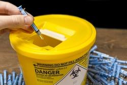 Needles being put ito a sharps bin