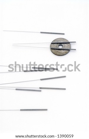 Needles for acupuncturists.  Shown with asian coin isolated on white.