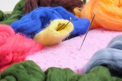 needles for felting, sponge and skeins of wool on the table, the process of felting from wool, handicraft concept close up