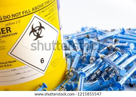 Needles next to a sharps bin