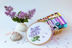 Needlework. A vase of blooming lilac and hand embroidery with satin ribbons on a white table. Sets of colored ribbons and accessories for embroidery in a wicker basket (embroidery are made by me)