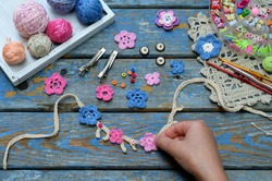 Needlework accessories for creating crocheted jewelry. Step 2 - sew crocheted flowers to bracelet or chain. DIY project. Small business. Income from hobby