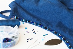 Needlework and hobbies. Beautiful hand embroidery with beads and glass beads on top of clothes on a white background. Beads and bugles next to the needles, needle-threader and box