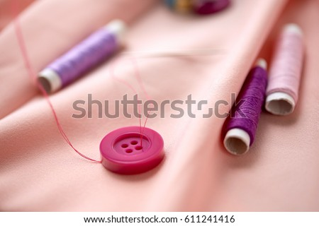 needlework and tailoring concept - sewing buttons, spools of thread and cloth