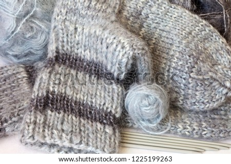 Needlework. Hand-knit warm socks made from fluffy natural mohair gray yarn and the five needles for knitting