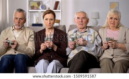 Needy senior people holding money looking camera, financial instability, crisis