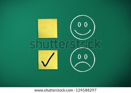negative feedback rapresentated by emoticons on green chalk board - stock photo
