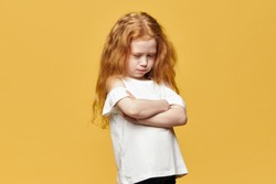 Negative human emotions, reactions and feelings. Isolated shot of moody displeased angry little girl crossing arms on her chest, pouting lips, having offended facial expression, being capricious