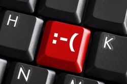negative smilie on red computer keyboard button showing bad feelings concept