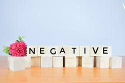 NEGATIVE word written on wood block.  Negative concept.