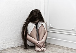 Neglected lonely child against the white wall.  Little girl crying in the corner. Violence concept.