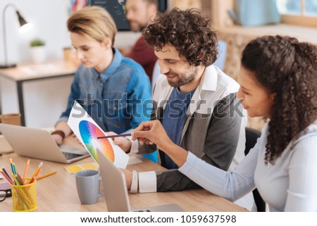 Negotiating. Good-looking content curly-haired man smiling and looking at a sheet of paper while sitting at the table with his colleagues