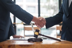 Negotiation of legal agreements. Businessmen and lawyers join hands after the negotiation ends.