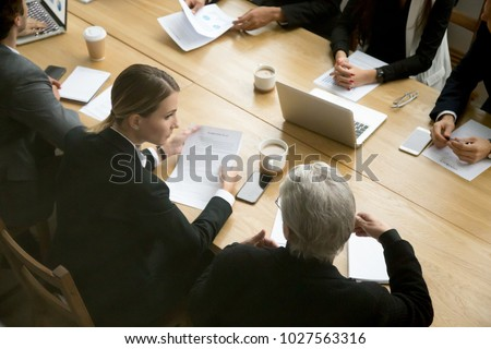 Negotiations concept, different businesspeople discussing deal details at group meeting, young and senior partners team thinking talking consulting about contract sitting at conference office table
