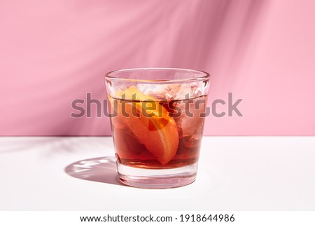 Negroni cocktail over pink background. Cocktail in rox glass in daylight with palm leaf hard shadow. Summer, tropical, fresh cocktail concept.