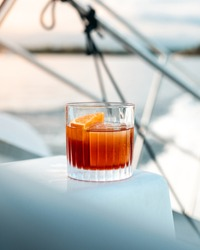 Negroni cocktail with a large ice cube on a boat (yacht)
