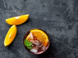 Negroni cocktail with ice and orange on dark background