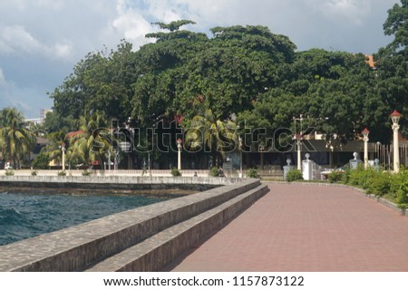 Negros Oriental, Philippines; August 12, 2018: A newly built promenade along Dumaguete City's boulevard, going to the city's port. Across the street is a portion of the Silliman University campus #1157873122