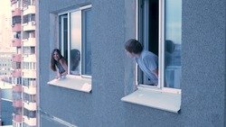 Neighbors talk to each other from the window. Young happy couple conversing in window. Neighbors concept. Young couple having a conversation while looking at each other over a window background