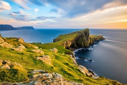 Neist Point Lighthouse on the Isle of Skye bathed in golden light from the setting sun.