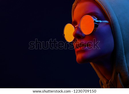 Neon close up portrait of young woman in round sunglasses and hoodie. Studio shot  #1230709150