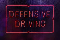 Neon Defensive Driving Sign in Wet Window