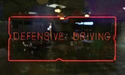 Neon Defensive Driving Sign in Wet Window of Restaurant