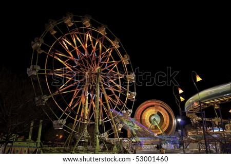 Neon ferris wheels an carnivals rides brighten up the night sky.