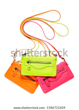 Neon handbags multiple colors stacked on white background