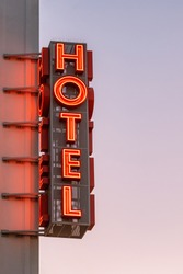 Neon hotel sign on the building corner against the sunset sky Empty copy space for inscription. Vintage sign. Vertical hotel sign