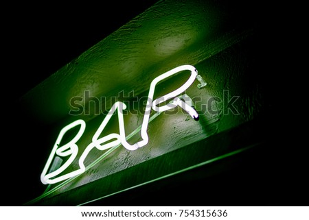 Neon inscription BAR on the wall. Neon inscription BAR in different colors. Multicolored neon inscription BAR on dark background #754315636