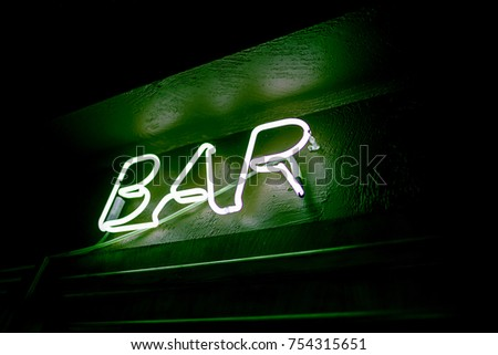 Neon inscription BAR on the wall. Neon inscription BAR in different colors. Multicolored neon inscription BAR on dark background #754315651