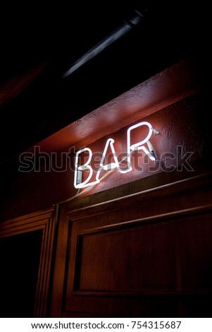 Neon inscription BAR on the wall. Neon inscription BAR in different colors. Multicolored neon inscription BAR on dark background #754315687
