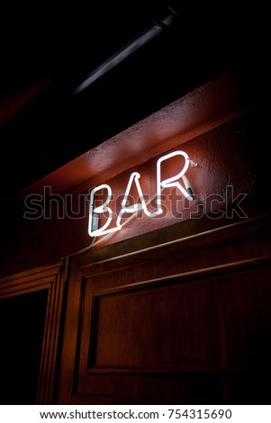 Neon inscription BAR on the wall. Neon inscription BAR in different colors. Multicolored neon inscription BAR on dark background #754315690