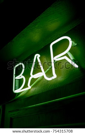 Neon inscription BAR on the wall. Neon inscription BAR in different colors. Multicolored neon inscription BAR on dark background #754315708