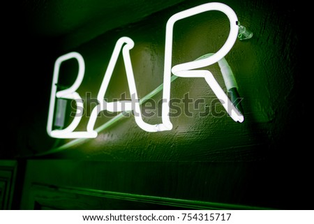 Neon inscription BAR on the wall. Neon inscription BAR in different colors. Multicolored neon inscription BAR on dark background #754315717