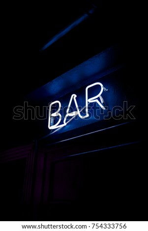 Neon inscription BAR on the wall. Neon inscription BAR in different colors. Multicolored neon inscription BAR on dark background #754333756