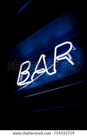 Neon inscription BAR on the wall. Neon inscription BAR in different colors. Multicolored neon inscription BAR on dark background #754333759