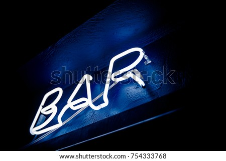 Neon inscription BAR on the wall. Neon inscription BAR in different colors. Multicolored neon inscription BAR on dark background #754333768