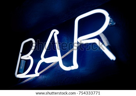 Neon inscription BAR on the wall. Neon inscription BAR in different colors. Multicolored neon inscription BAR on dark background #754333771