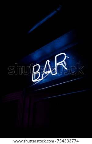 Neon inscription BAR on the wall. Neon inscription BAR in different colors. Multicolored neon inscription BAR on dark background #754333774