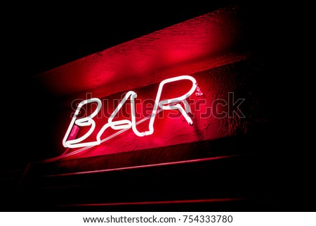 Neon inscription BAR on the wall. Neon inscription BAR in different colors. Multicolored neon inscription BAR on dark background #754333780